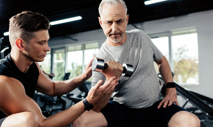Personal Trainer helping an older adult with light weights