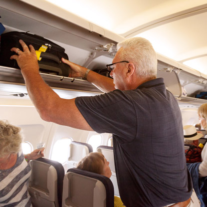 Properly putting luggage in the overhead bin compartment of a plane